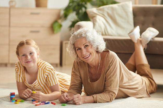 Portrait de jolie fille aux cheveux rouges jouant avec des blocs colorés en position couchée sur le sol avec grand-mère dans un intérieur confortable