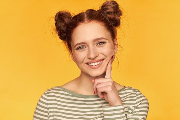 Portrait de jolie fille aux cheveux roux avec deux petits pains. avoir l'air ludique et toucher sa joue. porter un pull rayé et regarder isolé, gros plan sur mur jaune
