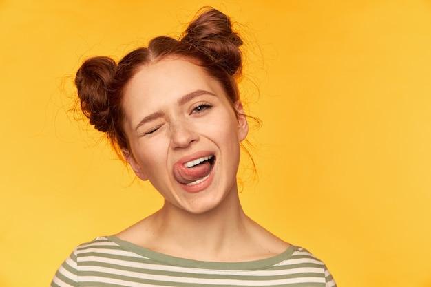 Portrait de jolie fille aux cheveux roux avec deux petits pains. ayez une humeur enjouée et idiote. porter un pull rayé, clin d'oeil et montrer une langue isolée, gros plan sur mur jaune