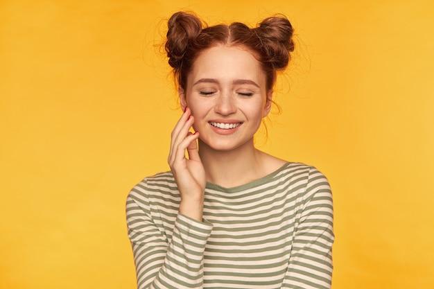 Portrait de jolie fille aux cheveux roux avec deux petits pains. porter un pull rayé et sourire avec les yeux fermés, toucher sa joue du bout des doigts. stand isolé sur mur jaune