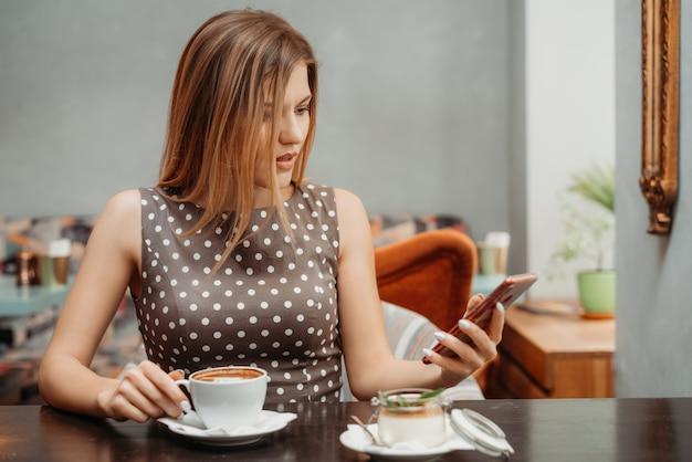 Portrait de jolie fille aux yeux ouverts aux cheveux bruns lisant quelque chose sur son téléphone portable à table de restaurant