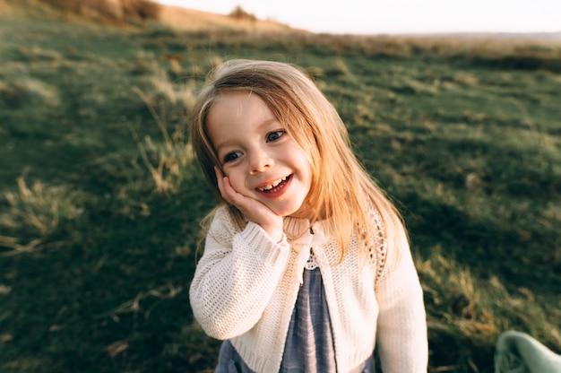 Portrait d'une jolie fille belle et heureuse qui traverse le champ ensoleillé