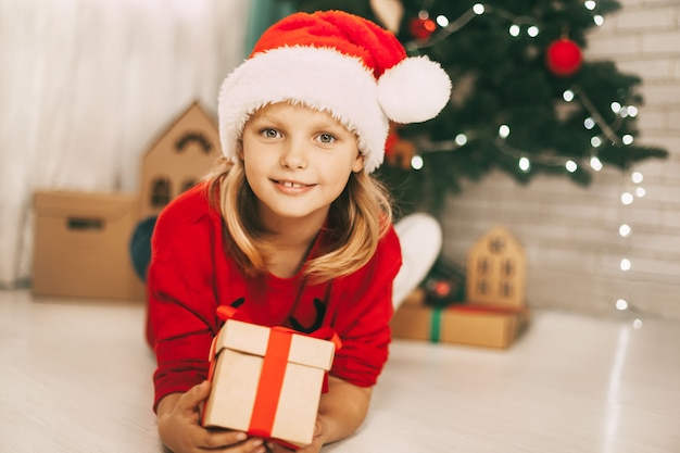 Portrait d'une jolie fille blonde dans un bonnet de noel, allongé sur le sol avec un cadeau dans ses mains