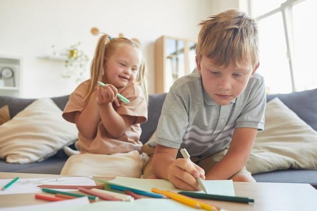 Portrait de jolie fille blonde trisomique en riant joyeusement en regardant son frère dessin à la maison, copiez l'espace