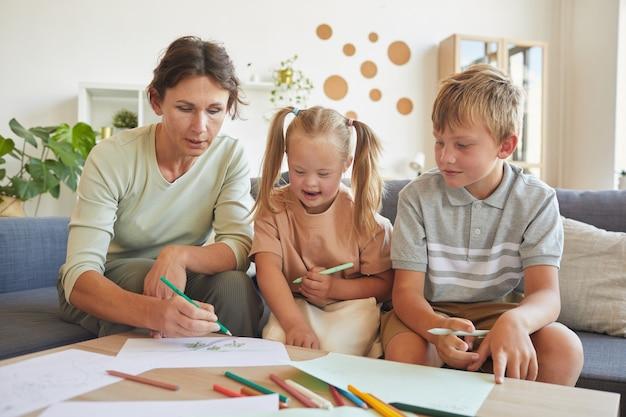 Portrait de jolie fille blonde trisomique riant joyeusement tout en se rapprochant de sa mère et son frère à la maison