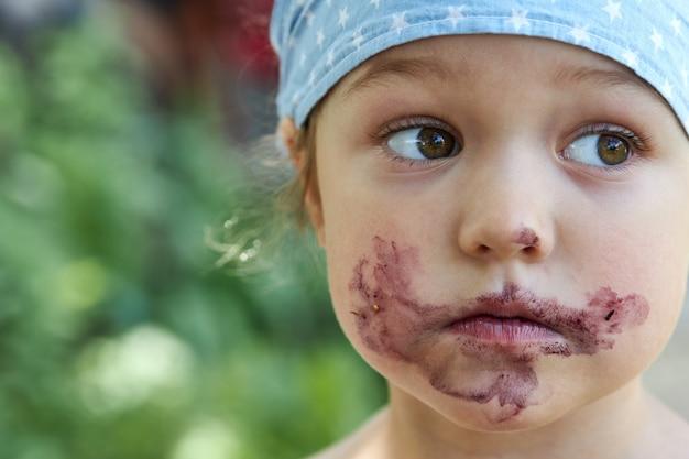 Portrait d'une jolie fille avec une bouche sale après avoir mangé des baies de mûrier