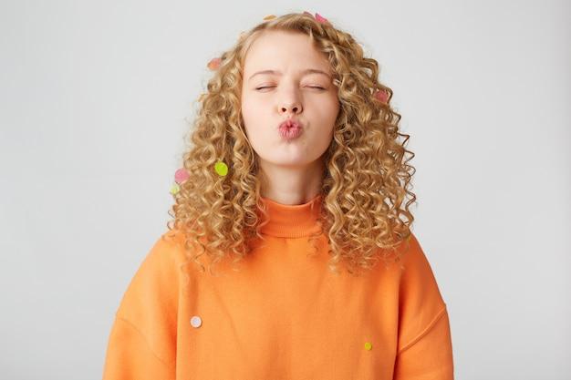 Portrait de jolie fille bouclée en pull orange avec un baiser d'air soufflant avec des lèvres boudeuses et les yeux fermés isolés sur un mur blanc