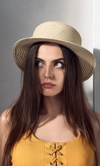 Portrait de jolie fille bouleversée portant un chapeau de paille et levant les yeux en pensant