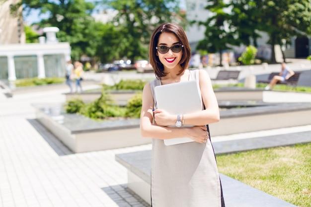 Un portrait de jolie fille brune en robe grise debout dans le parc de la ville. elle tient un ordinateur portable et sourit à la caméra.