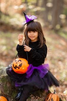 Portrait d'une jolie fille brune vêtue d'une robe noire d'halloween avec un panier de bonbons