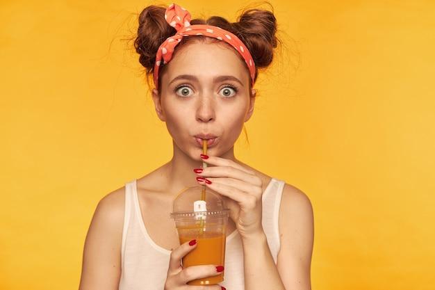 Portrait de jolie fille charmante avec deux petits pains et de grands yeux. portant un débardeur blanc et un serre-tête à pois rouges. boire une gorgée de jus sain. isolé sur mur jaune