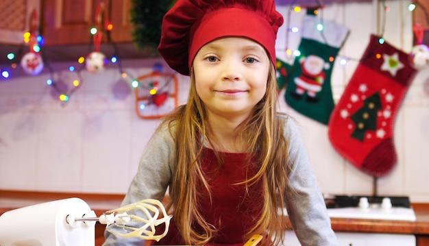 Portrait de jolie fille chef avec une pâte dans le bol. sur la table sont un mélangeur électrique, orange, différents ingrédients pour la pâte