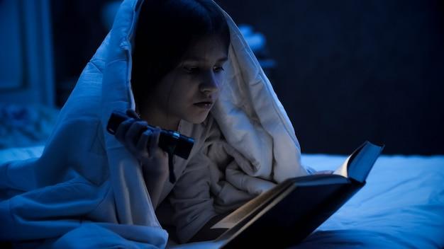 Portrait De Jolie Fille Couvrant Avec Une Couverture Et Un Livre De Lecture Avec Une Torche Lumineuse. Photo Premium