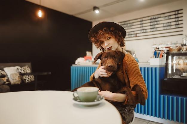 Portrait d'une jolie fille dans des vêtements à la mode et un chapeau est assis avec un chiot dans ses bras dans un café confortable