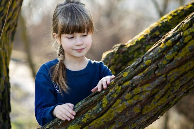 Portrait d'une jolie fille debout près d'un tronc d'arbre