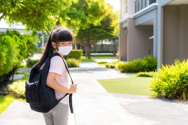 Portrait de jolie fille de l'école primaire en masque médical devant la maison