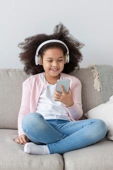 Portrait de jolie fille, écouter de la musique à la maison