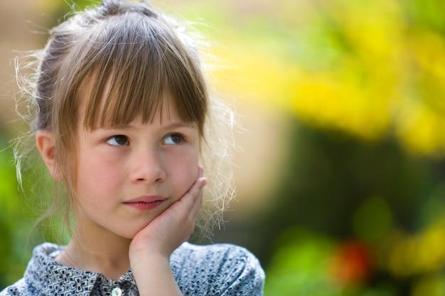 Portrait de jolie fille enfant pensif jolie à l'extérieur sur floue ensoleillée coloré brillant