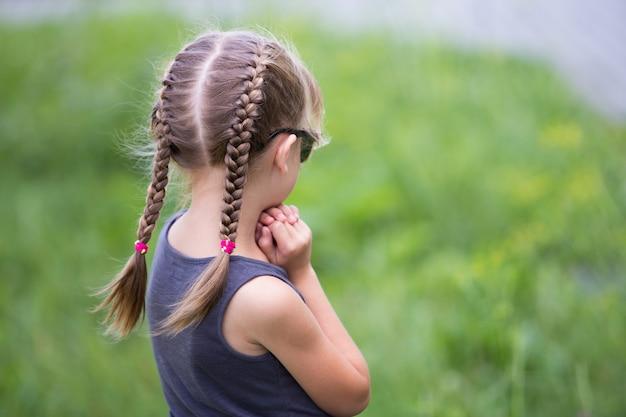 Portrait de jolie fille enfant avec des tresses dans les cheveux à l'extérieur en été.