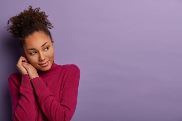 Portrait de jolie fille ethnique sensuelle se penche la tête sur les mains, regarde sérieusement de côté, admire quelque chose avec plaisir, porte un col roulé bordeaux, isolé sur un mur violet, a des pensées profondes