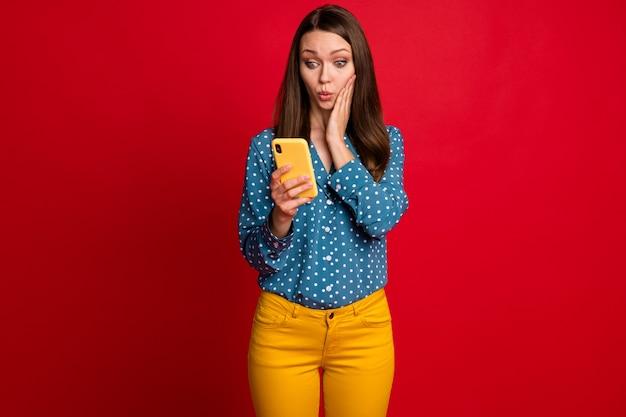 Portrait d'une jolie fille étonnée à l'aide de la cellule de navigation sur les actualités smm lèvres moue isolées sur fond de couleur rouge vif