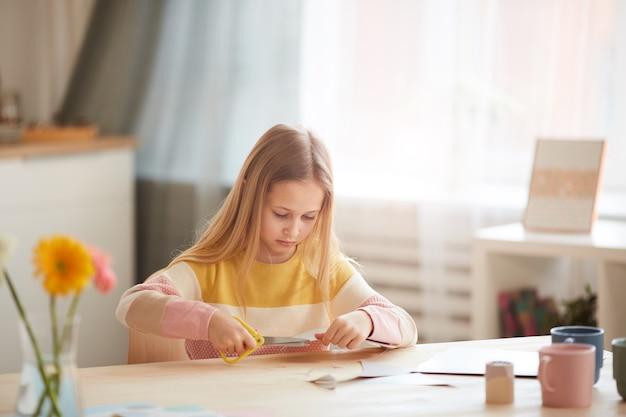 Portrait de jolie fille faisant des cartes de vœux pour la fête des mères ou la saint-valentin alors qu'il était assis à table dans un intérieur confortable, copiez l'espace