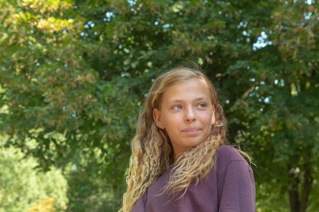 Portrait d'une jolie fille sur fond de verdure estivale