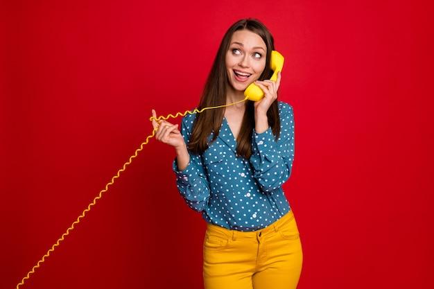 Portrait d'une jolie fille gaie parlant le récepteur du combiné appelant un ami isolé sur un fond de couleur rouge vif