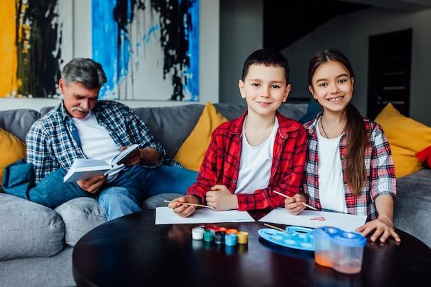 Portrait de jolie fille et garçon peignant à la gouache colorée pendant que leur grand-père lit son livre. journée familiale.