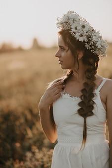 Portrait de jolie fille avec guirlande de fleurs et tresses en robe blanche dans le champ de l'été au coucher du soleil