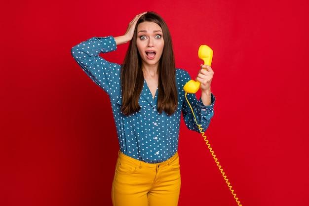 Portrait d'une jolie fille inquiète tenant dans la main des informations d'actualités du récepteur panique isolée fond de couleur rouge vif