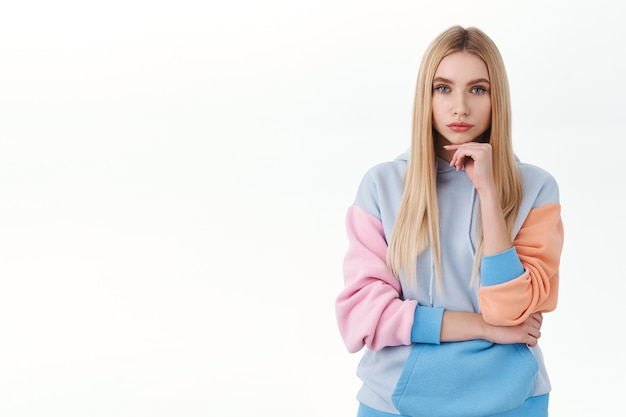 Portrait d'une jolie fille intelligente, déterminée et sérieuse, avec de longs cheveux blonds, l'air intéressé et réfléchi