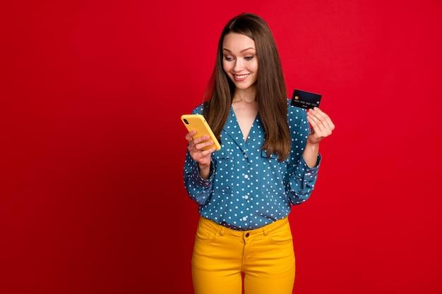 Portrait d'une jolie fille joyeuse et concentrée utilisant une application de service de paiement par carte bancaire isolée sur fond de couleur rouge vif