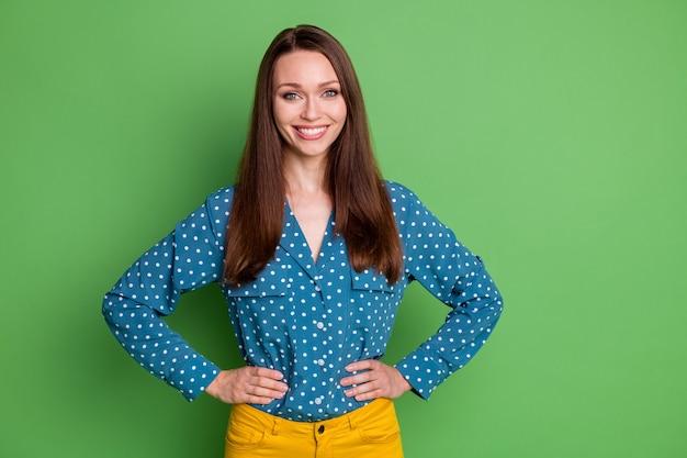 Portrait d'une jolie fille joyeuse portant un chemisier en pointillé mains sur les hanches isolées sur fond de couleur vert clair