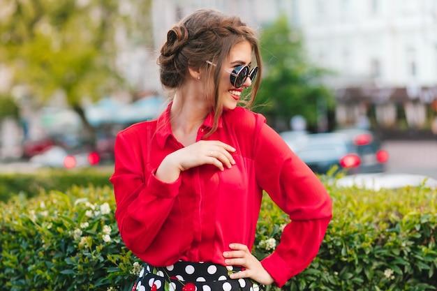 Portrait de jolie fille à lunettes de soleil posant à la caméra dans le parc. elle porte un chemisier rouge et une belle coiffure. elle sourit sur le côté.