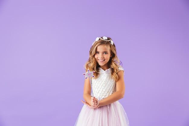 Portrait d'une jolie fille mignonne souriante vêtue d'une robe de princesse isolée sur mur violet, tenant la baguette magique