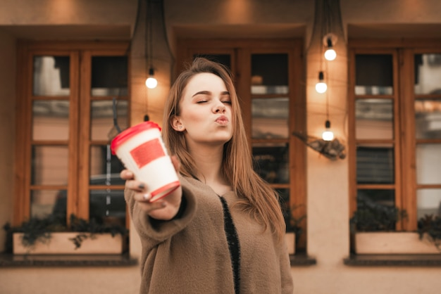 Portrait d'une jolie fille montre un verre de café en papier sur le fond d'un mur de restaurant marron