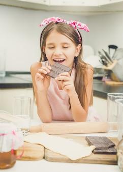 Portrait de jolie fille mordant une barre de chocolat noir dans la cuisine