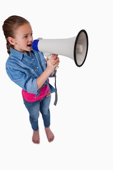 Portrait d'une jolie fille parlant à travers un mégaphone