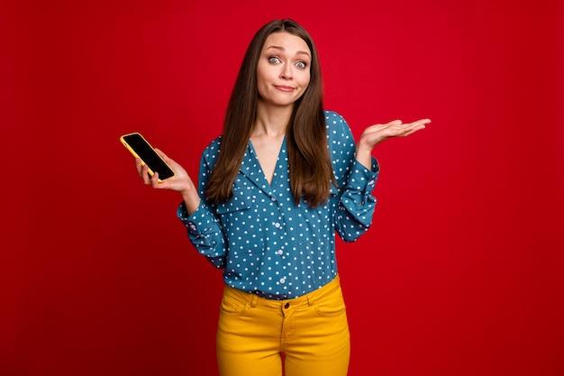 Portrait de jolie fille perplexe à l'aide de l'appareil en haussant les épaules fond de couleur rouge vif isolé