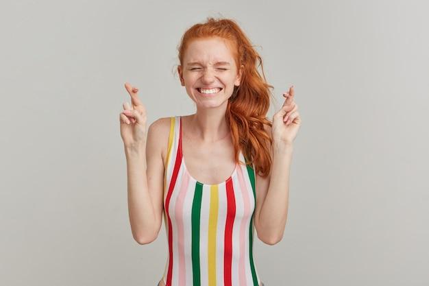 Portrait de jolie fille plissant les yeux avec une queue de cheval au gingembre et des taches de rousseur, portant un maillot de bain coloré à rayures