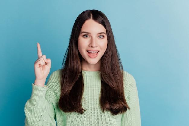 Portrait d'une jolie fille pointant le doigt vers le visage excité suggère un espace vide de bannière