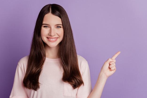 Portrait d'une jolie fille pointant du doigt côté espace vide sur fond violet