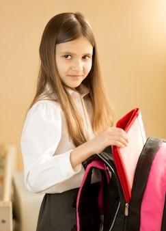 Portrait de jolie fille prenant le fichier de son sac d'école