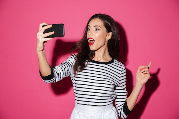 Portrait d'une jolie fille prenant un selfie