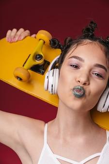 Portrait d'une jolie fille punk avec une coiffure bizarre et un rouge à lèvres foncé tenant une planche à roulettes tout en écoutant de la musique avec des écouteurs isolés sur un mur rouge
