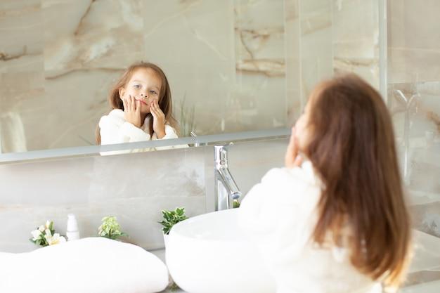 Portrait d'une jolie fille qui se regarde dans le miroir en blouse blanche avec une licorne dans une salle de bain lumineuse avec fenêtre. hygiène. routine matinale. pureté. comme mère. photo de haute qualité