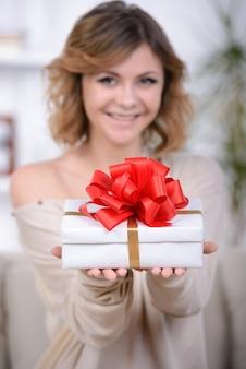 Portrait de jolie fille reçoit une boîte cadeau.