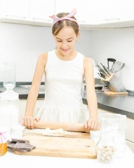 Portrait de jolie fille rouler et pétrir la pâte sur planche de bois