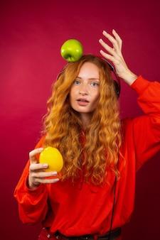 Portrait d'une jolie fille rousse aux longs cheveux bouclés avec des taches de rousseur, avec une orange, une pomme et des écouteurs.